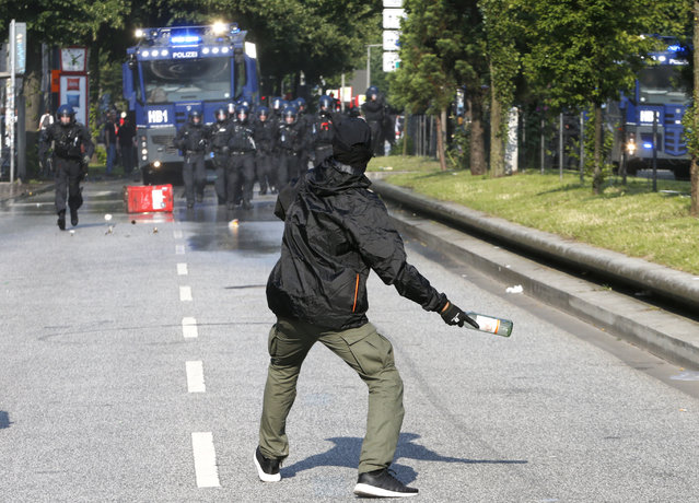 A demonstrator throws a bottle towards police on the first day of the G-20 summit in Hamburg, northern Germany, Friday, July 7, 2017. The leaders of the group of 20 meet July 7 and 8. (Photo by Michael Probst/AP Photo)