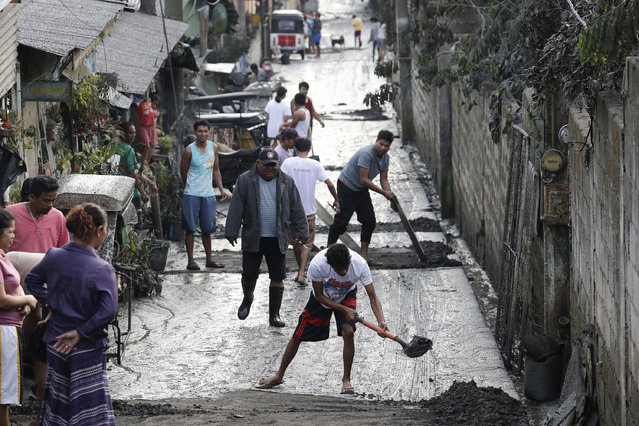 Residents clean ash outside their homes as Taal Volcano still spews ash on Monday January 13, 2020, in Tagaytay, Cavite province, south of Manila, Philippines. (Photo by Aaron Favila/AP Photo)