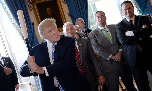 "US President Donald Trump examines US- made products from all 50 states, including a Marucci baseball bat, in the Blue Room of the White House during a ""Made in America"" product showcase event in Washington, DC, on July 17, 2017. (Photo by Olivier Douliery/AFP Photo)"