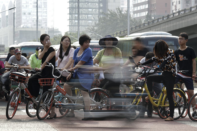 Cyclists and motorists wait to cross a traffic intersection at the Central Business District during the morning rush hour in Beijing, Monday, July 17, 2017. China's economic growth held steady in the latest quarter, boosted by trade and consumer spending, despite concerns about a possible impending slowdown. (Photo by Andy Wong/AP Photo)