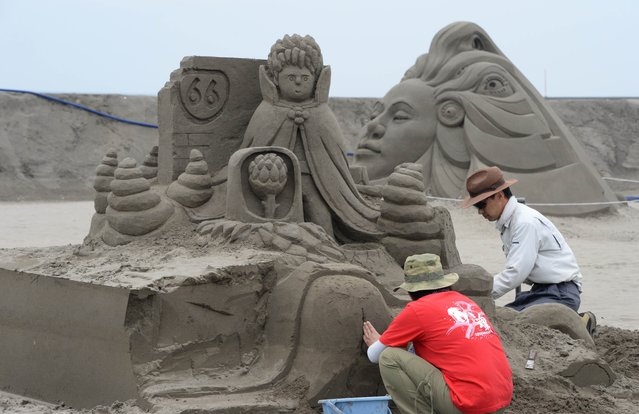 Sand artists build their sculptures at Yasashigaura beach in Asahi, Chiba prefecture on July 13, 2014. The Asahi Sand Sculpture exhibition will run from July 15 until August 7 with over 50,000 visitors expected. (Photo by Toshifumi Kitamura/AFP Photo)