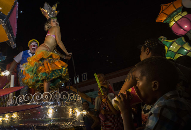 In this July 25, 2015 photo, revelers parade during carnival celebrations in Santiago, Cuba. Cuban cities are seeing stagnant visitor numbers despite the dramatic surge in overall tourism set off by the announcement of detente between the U.S. and Cuba. (Photo by Ramon Espinosa/AP Photo)