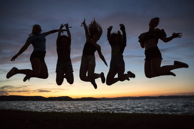 Revellers jump in the air on the shore of Lake Balaton during the opening of Balaton Sound music festival in Zamardi, 110 km southwest of Budapest, Hungary, 06 July 2016. The festival runs from 06 to 10 July. (Photo by Balazs Mohai/EPA)