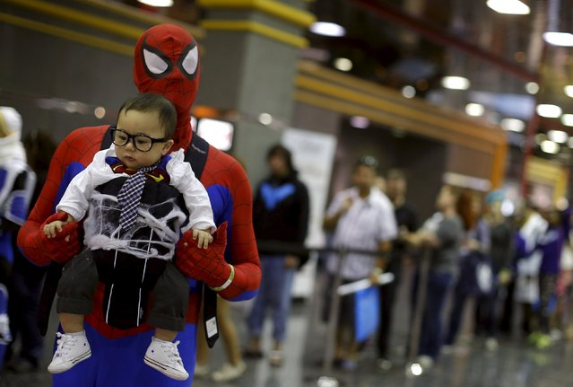 """Mike Tester dressed up as """"Spiderman"""" carries his son Owen dressed as """"Clark Kent"""" through the hallways at Wizard World Comic Con in Chicago, Illinois, United States, August 22, 2015. (Photo by Jim Young/Reuters)"""