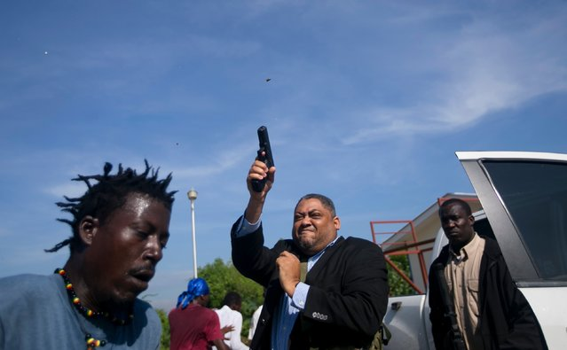 Ruling party Senator Ralph Fethiere fires his gun outside Parliament as he arrives for a vote on the ratification of Fritz William Michel's nomination as prime minister in Port-au-Prince, Haiti, Monday, September 23, 2019. Opposition members confronted ruling-party senators, and Fethiere pulled a pistol when protesters rushed at him and members of his entourage. The vote was cancelled. (Photo by Dieu Nalio Chery/AP Photo)