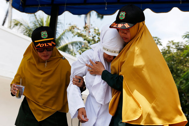 Sharia Police escort an Acehnese woman before she is caned in public for having s*x outside of marriage in Banda Aceh, Aceh, Indonesia, 02 March 2020. (Photo by Hotli Simanjuntak/EPA/EFE)