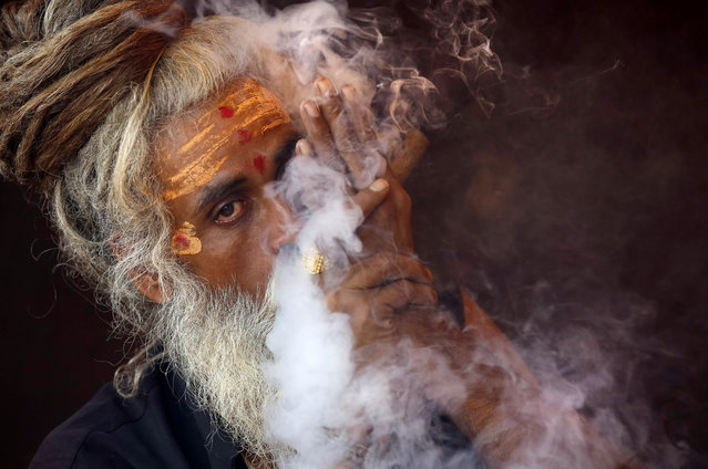 A Naga sadhu, or naked Hindu holy man, smokes hashish inside his tent during Kumbh Mela, or Pitcher festival, at Trimbakeshwar, India, Friday, August 28, 2015. Hindus believe taking a dip in the waters of a holy river during the festival will cleanse them of their sins. The festival is held four times every 12 years. (Photo by Rajanish Kakade/AP Photo)