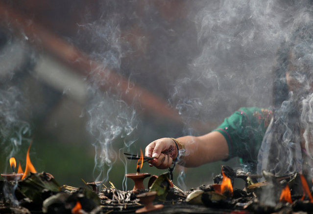 A devotee light incenses while offering prayers at Pashupatinath temple to mark the Shrawan Sombar festival in Kathmandu, Nepal, July 18, 2016. (Photo by Navesh Chitrakar/Reuters)
