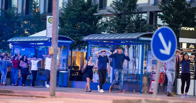 Evacuated people from the shopping mall walk with their hands up in Munich on July 22, 2016 following a shooting earlier. At least one person has been killed and 10 wounded in a shooting at a shopping centre in Munich on Friday, German police said. (Photo by AFP Photo/Stringer)