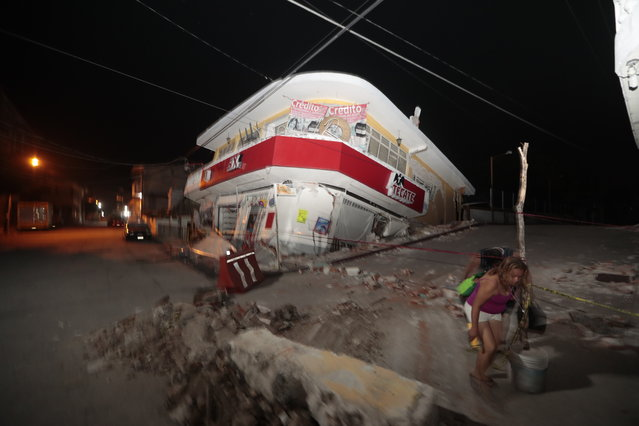A woman walks past a collapsed building after a 7.1 earthquake, in Jojutla, Morelos state, Mexico, Tuesday, September 19, 2017. The earthquake stunned central Mexico, killing more than 100 people as buildings collapsed in plumes of dust. (Photo by Eduardo Verdugo/AP Photo)