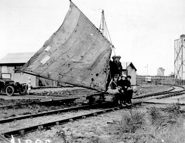 A group of men travelling along a railway track using a sail-driven wagon at Spurn Head, England, October 1922.
