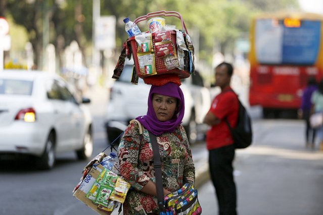 A woman street vendor who sells drinks and food walks across the street in Jakarta September 1, 2015. Global economic growth is likely to be weaker than earlier expected, the head of the International Monetary Fund said on Tuesday, due to a slower recovery in advanced economies and a further slowdown in emerging nations. (Photo by Reuters/Beawiharta)