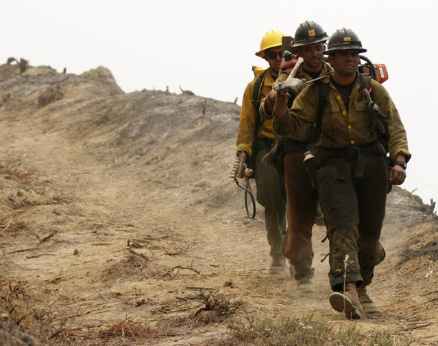 A trio of Angeles National Forest firefighters from the Valerymo Hotshots walk back to their truck as the Sand Fire burns near Wildlife Waystation on Little Tujunga Canyon Road on Saturday, July 23, 2016. (Photo by Katharine Lotze/The Santa Clarita Valley Signal via AP Photo)