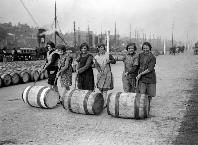 Yarmouth fisher-girls pushing barrels of herring along the quayside using long poles, 1929. (Photo by Fox Photos)