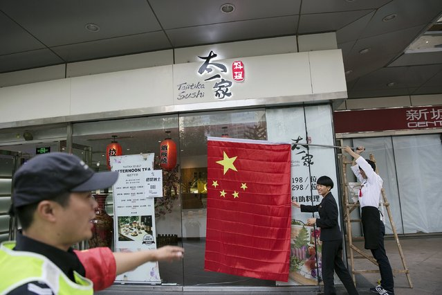 A Chinese flag is placed outside a sushi bar in central Beijing September 2, 2015 as people in the capital prepares to mark the end of World War Two. (Photo by Damir Sagolj/Reuters)