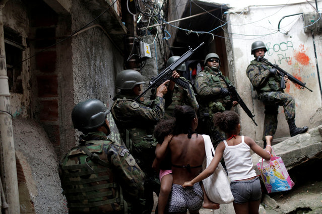 Soldiers take up a position during an operation after violent clashes between drug gangs in Rocinha slum in Rio de Janeiro, Brazil on September 22, 2017. (Photo by Ricardo Moraes/Reuters)