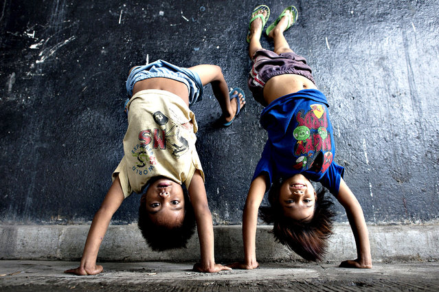 Children display their acrobatic skills at an underpass in Manila on August 28, 2014 near where informal settlers' homes were recently demolished. (Photo by Noel Celis/AFP Photo)