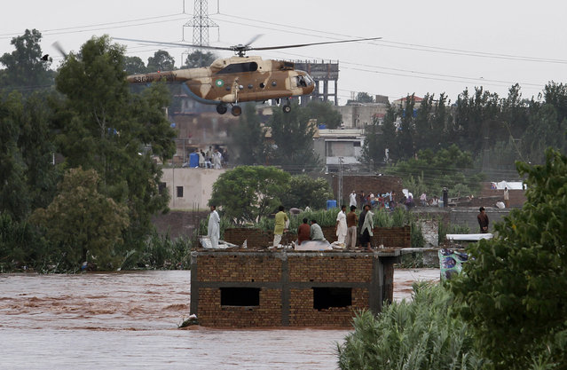 An Pakistani army helicopter hovers to rescue trapped people from a flooded area on the outskirts of Islamabad, Pakistan, Friday, September 5, 2014. (Photo by Anjum Naveed/AP Photo)