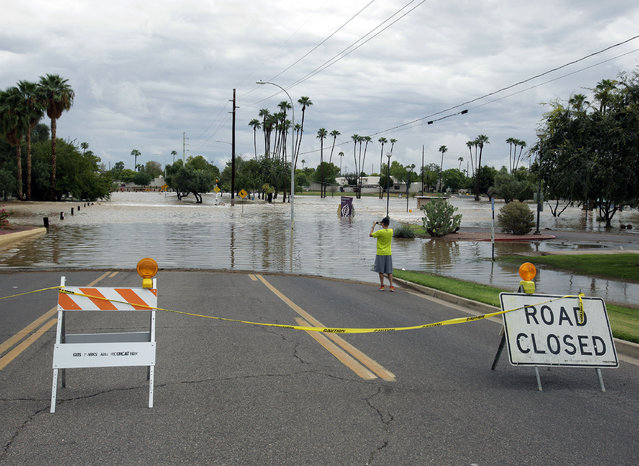 A man photographs a street closed because of flooding on Monday, September 8, 2014, in Scottsdale, Ariz. The remnants of Hurricane Norbert pushed into the desert Southwest and swamped Arizona Monday, breaking the previous record for rainfall in a single day in Phoenix. (Photo by Rick Scuteri/AP Photo)