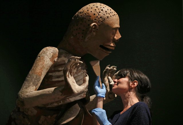 Australian Museum conservator Heather McKay inspects a piece depicting Mictlantecuhtli, God of Death and Lord of the Underworld, from the Aztecs exhibition in Sydney, Thursday, September 11, 2014. More than 200 stone, terra-cotta and other artifacts are on display showcasing the Aztec history and culture in the exhibition that opens Saturday and runs through to Feb. 1, 2015. (Photo by Rick Rycroft/AP Photo)