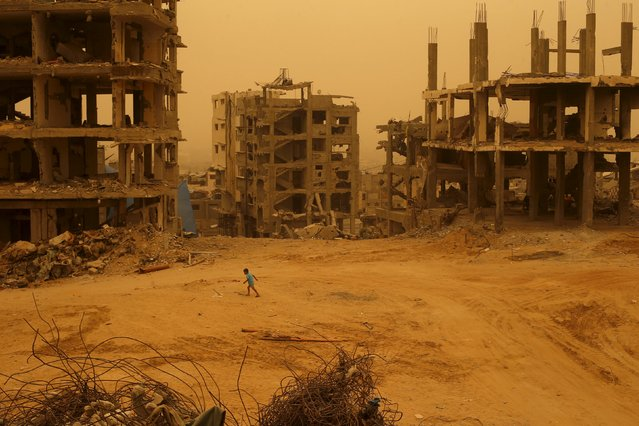 A Palestinian boy walks past houses, which witnesses said were destroyed by Israeli shelling during a 50-day war in 2014 summer, during a sandstorm in Gaza September 8, 2015. (Photo by Suhaib Salem/Reuters)