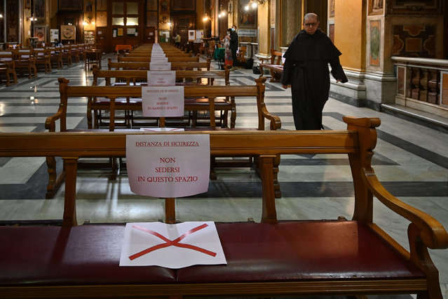 """Placards on benches read """"Security distancing, do not seat in this space"""" prior to a mass at the church of Santa Maria in Traspontina in Rome on May 18, 2020 during the country's lockdown aimed at curbing the spread of the COVID-19 infection, caused by the novel coronavirus. Restaurants and churches reopen in Italy on May 18, 2020 as part of a fresh wave of lockdown easing in Europe and the country's latest step in a cautious, gradual return to normality, allowing businesses and churches to reopen after a two-month lockdown. (Photo by Vincenzo Pinto/AFP Photo)"""