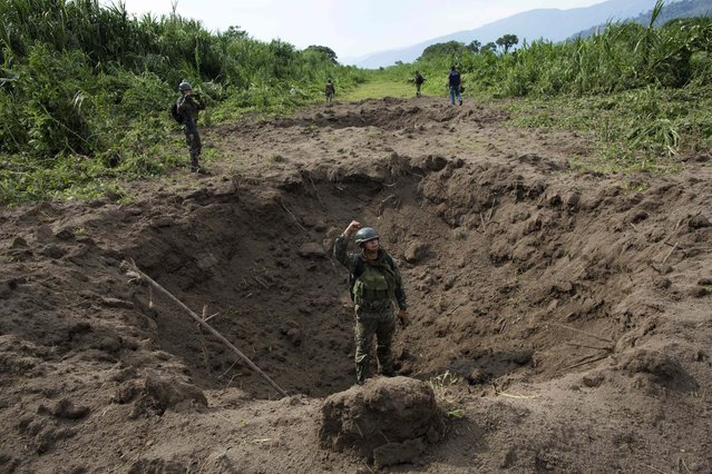 In this Friday, September 19, 2014 photo, a soldier signals to his commander while standing inside a crater created by explosives planted by Peruvian counternarcotics forces on part of a clandestine grassy airstrip, in the Valley of the Apurimac, Ene and Mantaro River Valleys, or VRAEM, the world's No. 1 coca-growing region in Ayacucho, Peru. According to official data, Peru has blown craters into 132 clandestine airfields this year, up from 110 last year. (Photo by Rodrigo Abd/AP Photo)