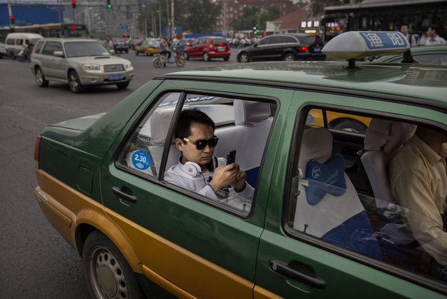 A Chinese man uses his smartphone as he sits in traffic in the back of a taxi on September 16, 2014 in Beijing, China. (Photo by Kevin Frayer/Getty Images)