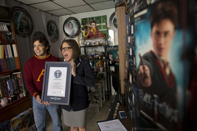 Johanna Hessling of Guinness World Records, right, presents Menahem Asher Silva Vargas, a 37 year old lawyer, with a certificate recognizing him as the title holder for the largest collection of Harry Potter memorabilia, at his home in Mexico City, Monday, September 29, 2014. (Photo by Rebecca Blackwell/AP Photo)