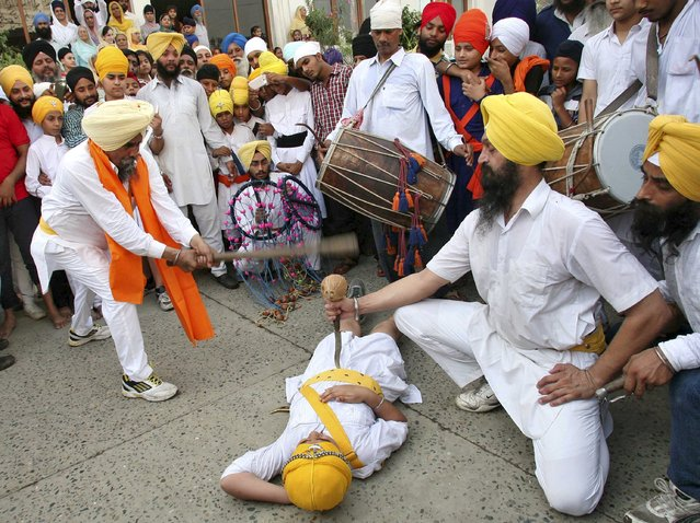 A Sikh performer breaks a coconut with a stick as he performs Gatkha, a traditional form of martial art, during a religious procession in Amritsar, India, September 14, 2015. The procession was carried out to celebrate the 411th anniversary of the installation of the Guru Granth Sahib, the religious book of Sikhs. (Photo by Munish Sharma/Reuters)