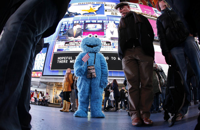 A man dressed as the character Cookie Monster watches TV screens in Times Square giving U.S presidential election results in New York November 6, 2012. (Photo by Carlo Allegri/Reuters)