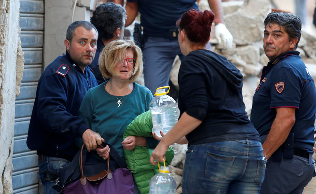 A woman (2nd L) cries after been rescued from her home following a quake in Amatrice, central Italy, August 24, 2016. (Photo by Remo Casilli/Reuters)