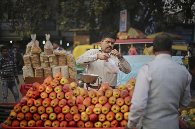 """In this November 15, 2017, photo, Ajay Kumar, 46, a fruit vendor sells apples outside a railway station in New Delhi, India. Kumar has been doing this job for more than 30 years, supporting his wife and four children. He said on days this month when the pollution has been bad he's covered his face and worn goggles. And the smog made him ill. """"I had a fever and a cough. My eyes hurt, my throat hurt and it was difficult to walk"""", he said. """"But I still had to muster the courage to work for my children, to feed them. Work has to be done. Work is important"""". (Photo by Altaf Qadri/AP Photo)"""