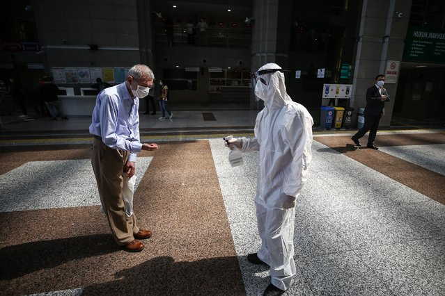 """An official wearing fully equipped protective suit sprays hand sanitizer at Istanbul Caglayan Justice Palace to stem the spread of COVID-19 pandemic as it is reorganized accordingly social distance rules before it reopens on 15th of June in Istanbul, Turkey on June 05, 2020. The government took a set of decisions to ease restrictions against the novel coronavirus (COVID-19) for the """"new normal"""" process. (Photo by Onur Coban/Anadolu Agency via Getty Images)"""