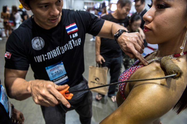"""In this photograph taken on November 9, 2017, a female bodybuilder holds still as a team member applies a tanning product to her upper body with a roller before she performs her routine in front of judges at a local bodybuilding competition in Bangkok. The room buzzes with excitement as dolled- up women adjust their glittering bikinis and prepare to strut across the stage before the panel of judges in a Bangkok suburb. But this is not your average Thai beauty pageant – it is a competition for the growing number of female bodybuilders challenging norms in kingdom where the pale, """"twig"""" physique has long been upheld as the standard of beauty. (Photo by Roberto Schmidt/AFP Photo)"""