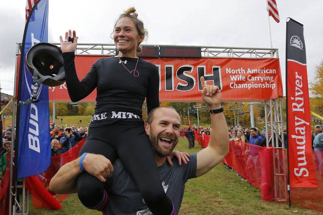 Christina Arsenault and Jesse Wall (R) celebrate after winning the North American Wife Carrying Championship at Sunday River ski resort in Newry, Maine October 11, 2014. REUTERS/Brian Snyder