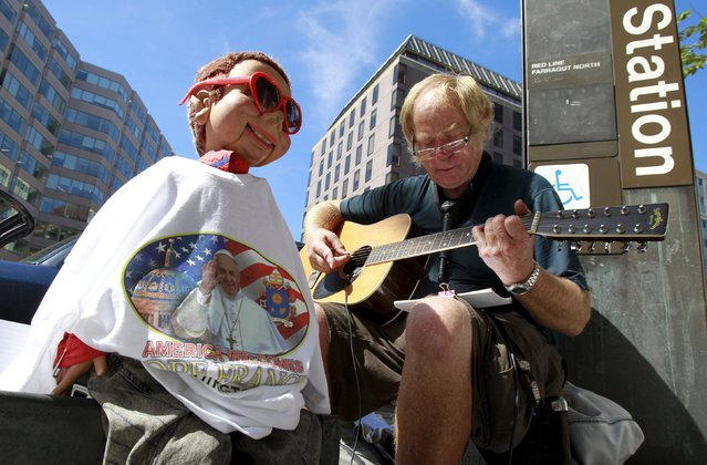 A street musician plays religious music with a doll wearing t-shirt with greetings for Pope Francis in Washington September 23, 2015. (Photo by Yuri Gripas/Reuters)