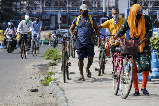 People wearing face masks cross a bridge with their cycles in Kolkata, India, Tuesday, July 14, 2020. (Photo by Bikas Das/AP Photo)