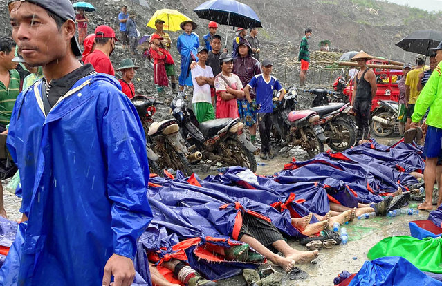 People gather near the bodies of victims of a landslide near a jade mining area in Hpakant, Kachine state, northern Myanmar Thursday, July 2, 2020. Myanmar government says a landslide at a jade mine has killed dozens of people. (Photo by Zaw Moe Htet/AP Photo)