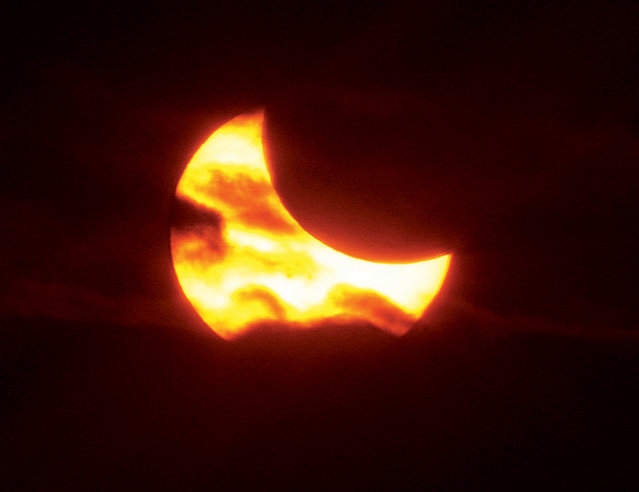 The moon passes between the earth and the sun Thursday, October 23, 2014, near the totality stage of a partial solar eclipse as seen from West Alton, Mo. Heavy clouds blocked the entire eclipse except for about 2 minutes when it found a view through an opening in the clouds. (Photo by John Badman/AP Photo/The Telegraph)