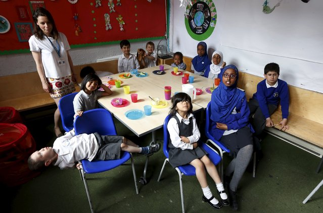 Students in Irena Chmura's Salusbury World class, which includes students from Year 1 to Year 6, pose in their classroom in London, Britain June 25, 2015. Salusbury World is a charity that supports refugee and asylum seeking children and families. Established in 1999, it was the first refugee centre to be set up within a primary school. (Photo by Suzanne Plunkett/Reuters)