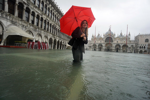 A woman wades through high water in Venice, Italy, 24 November 2019. (Photo by Andrea Merola/EPA/EFE)