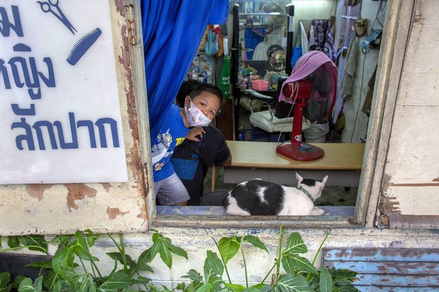A boy peeps out of a window at a barber saloon in Bangkok, Thailand, Tuesday, July 7, 2020. Daily life in the capital slowly returns to normal as Thai government has eased restrictions imposed weeks ago to combat the spread of COVID-19. Thailand has record zero coronavirus local transmission for over five weeks. (Photo by Gemunu Amarasinghe/AP Photo)
