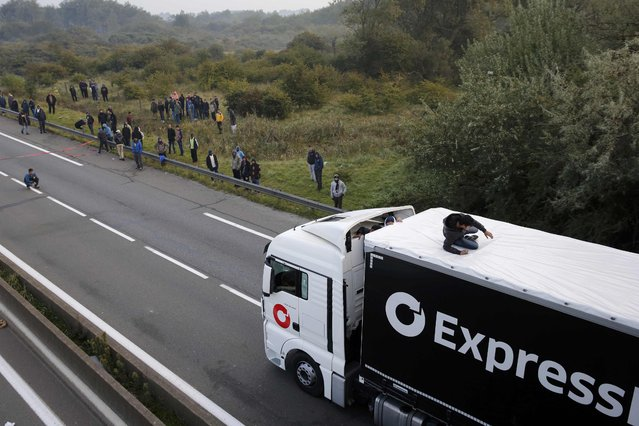 A migrant is seen on the roof of a lorry as groups of migrants gather along the road towards the ferry terminal in Calais, France, October 3, 2015. (Photo by Pascal Rossignol/Reuters)