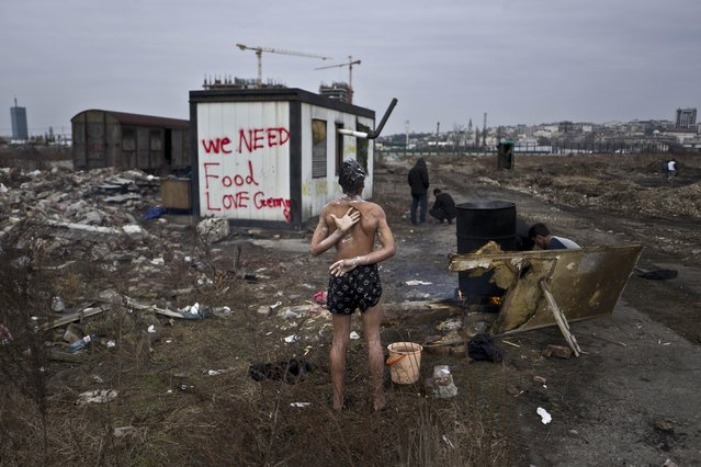 In this Saturday, February 11, 2017 photo, a 14-year old unaccompanied minor, a migrant from Afghanistan, showers on a cold day near an old train carriage where he and other migrants took refuge in Belgrade, Serbia. (Photo by Muhammed Muheisen/AP Photo)