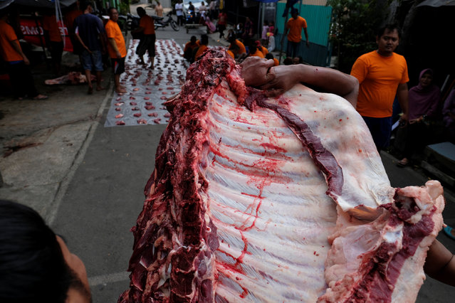 A man holds meat that will distributed to the poor during the Muslim holiday of Eid Al-Adha outside a mosque at Pasar Senin in Jakarta, Indonesia, September 12, 2016. (Photo by Reuters/Beawiharta)