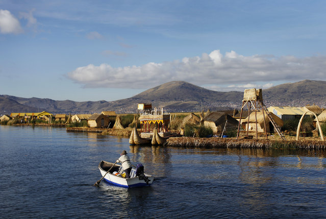 An Andean man rows a boat next to the shores of Uros islands at Lake Titicaca in Puno November 5, 2014. (Photo by Enrique Castro-Mendivil/Reuters)