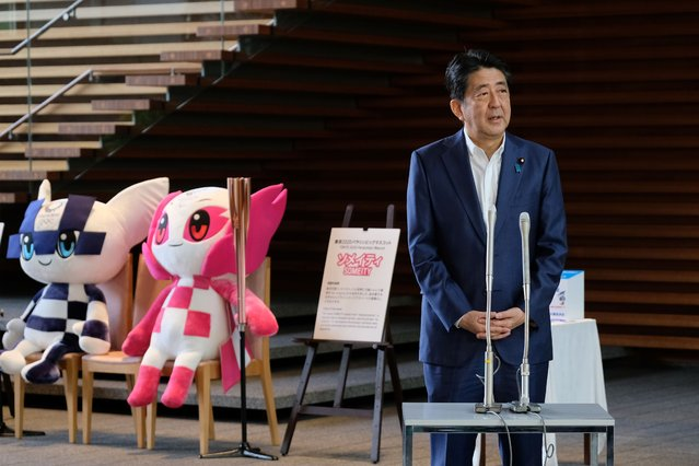 Japan's Prime Minister Shinzo Abe speaks to the media upon his arrival at the entrance of the Prime Minister's office, as Tokyo 2020 Olympic mascot Miraitowa (L), and Paralympic mascot Someity (2nd L) are seen on August 24, 2020. Abe earlier in the day returned to hospital on August 24 for more medical checks, a government spokesman said, a week after a first visit that fuelled growing speculation about his health. (Photo by Kazuhiro Nogi/AFP Photo)