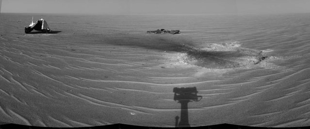 Opportunity gained this view of its own heat shield during the rover's 325th martian day (December 22, 2004). The main structure from the successfully used shield is to the far left. Additional fragments of the heat shield lie in the upper center of the image. The heat shield's impact mark is visible just above and to the right of the foreground shadow of Opportunity's camera mast. (Photo by NASA/JPL/The Atlantic)