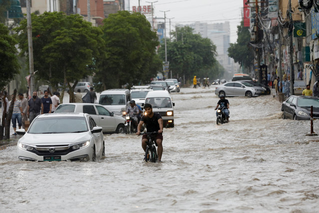Commuters ride past a flooded street during the monsoon rain, as the outbreak of the coronavirus disease (COVID-19) continues, in Karachi, Pakistan on August 25, 2020. (Photo by Akhtar Soomro/Reuters)